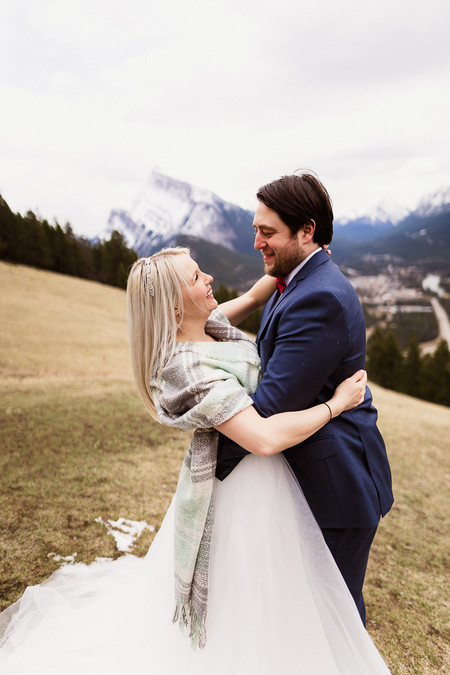 Having fun during Banff elopement photography overlooking the town of Banff
