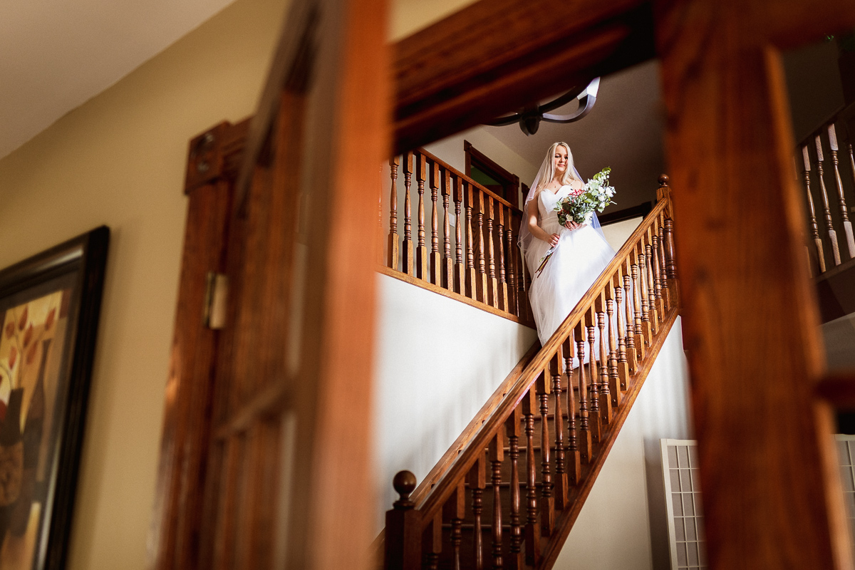 Bride walking down stairs for first look at Banff elopement photography