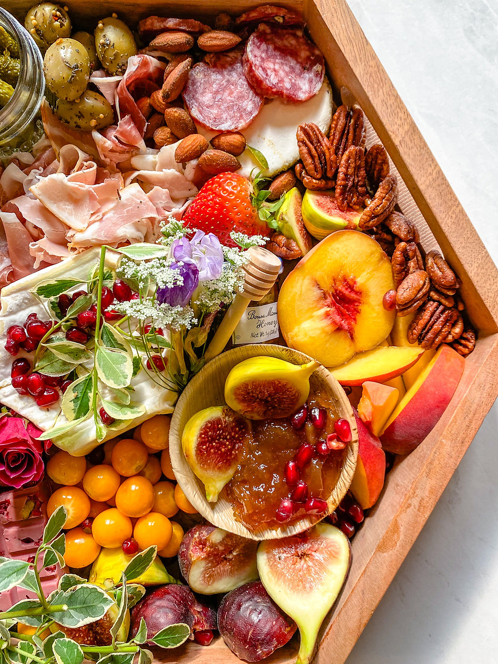 A hexagonal high walled wooden grazing board covered in cheese, meats, fruit, jams, and a spray of flowers