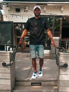 photo of Chef Andre Williams standing in jean shorts on a patio step