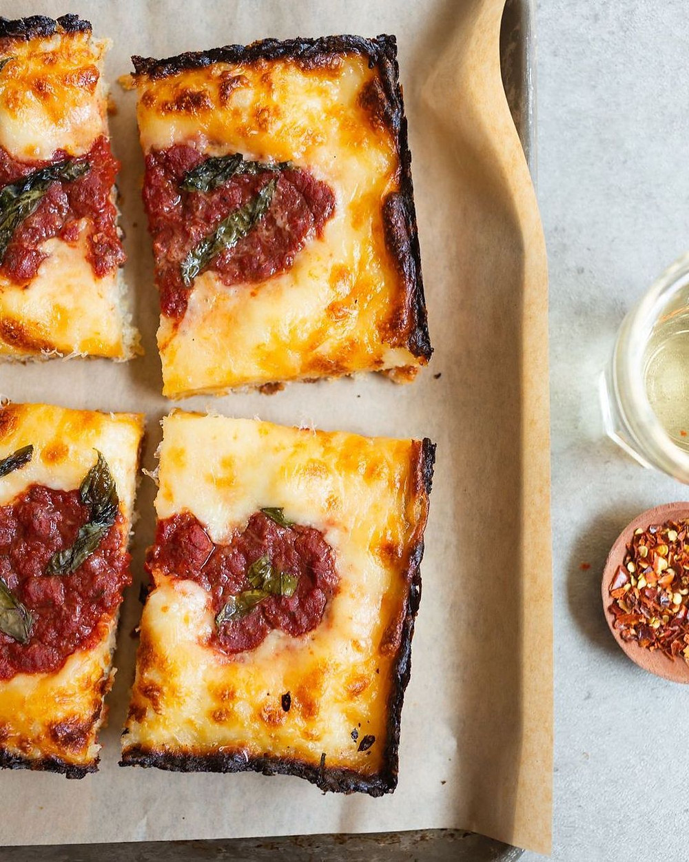 Detroit-style pizza on a tray with red pepper flakes in a small dish next to it