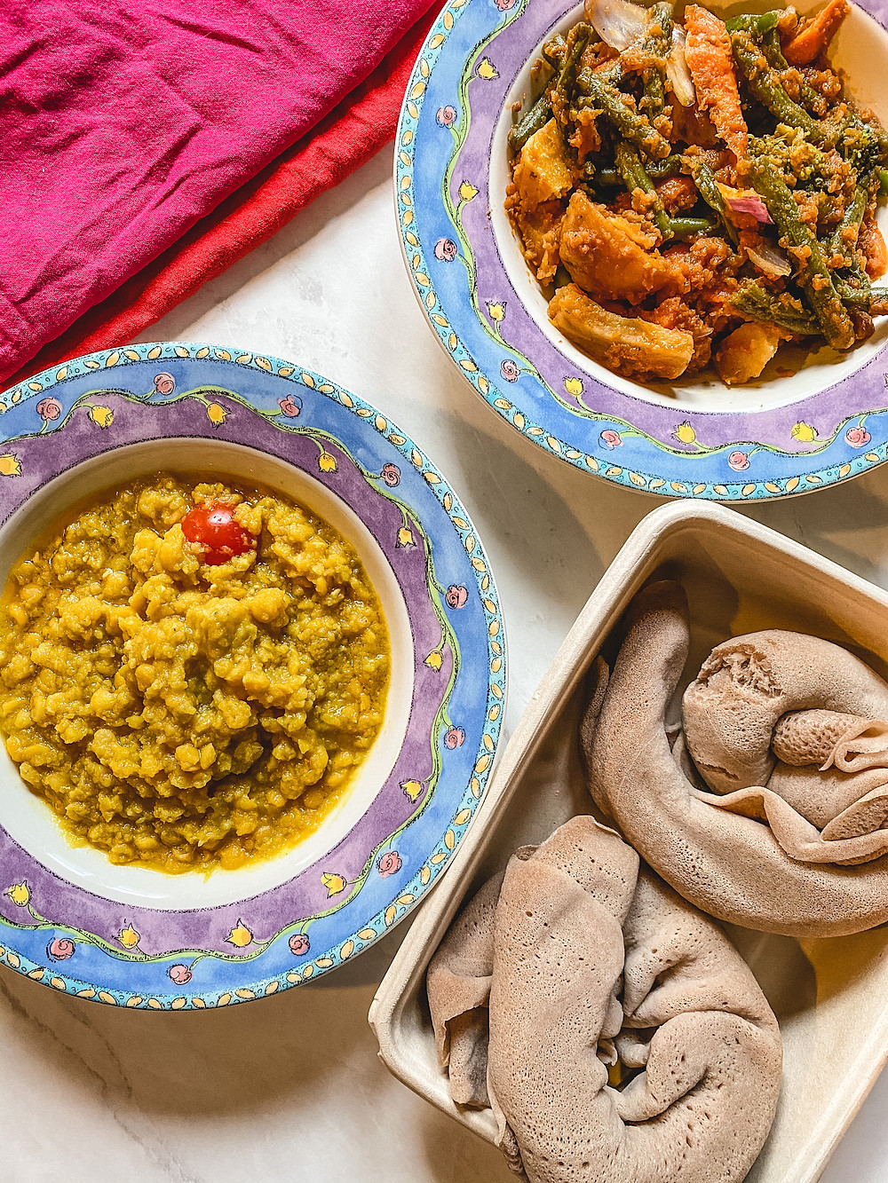 Ingera bread in a container, Ethiopian lentils in a bowl with a flowery blue rim, vegetables in a bowl with a flowery blue rim, and a red and pink cloth napkin arranged on a white table