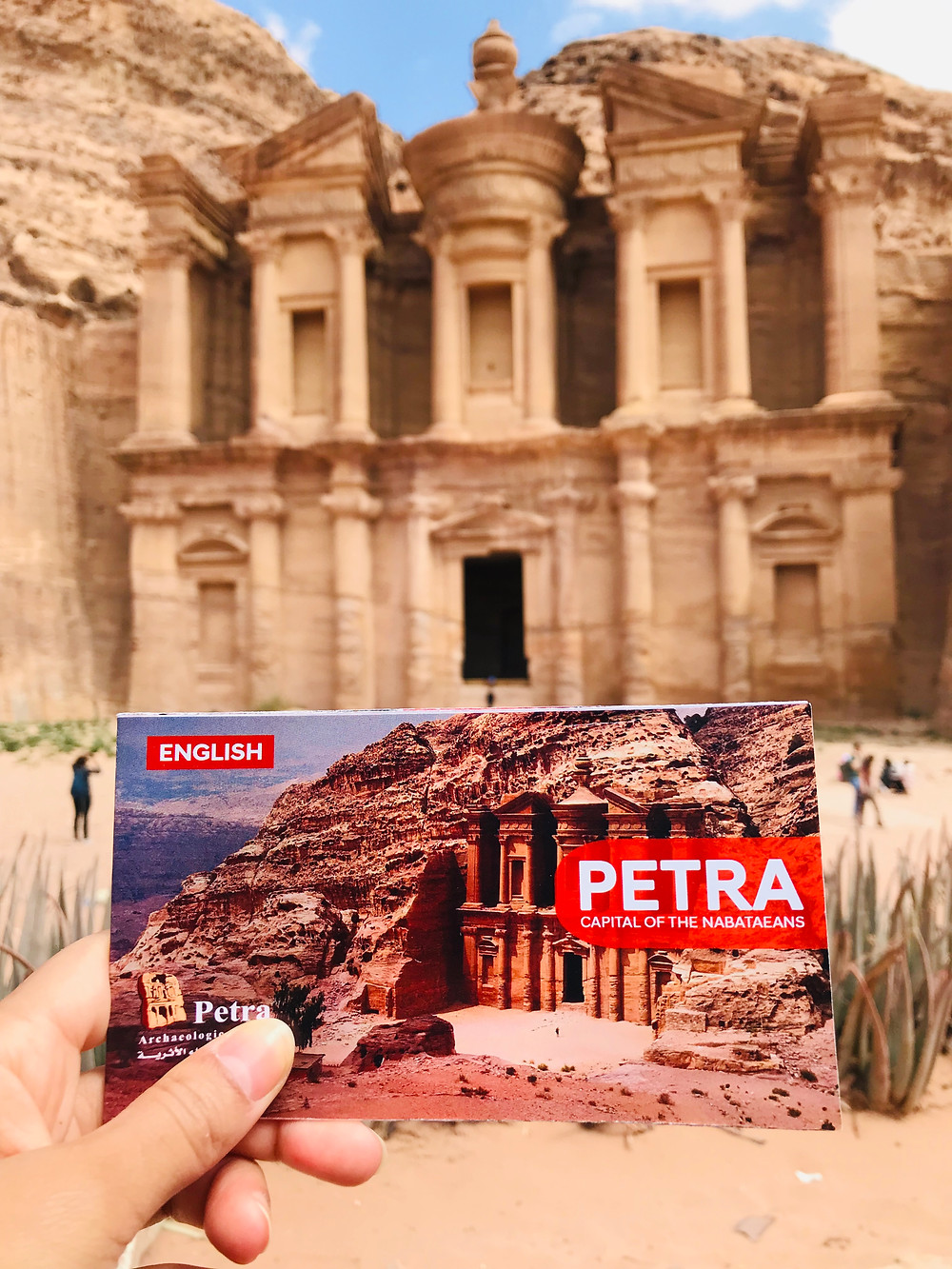 hand holding a Petra informational pamphlet in front of a building carved into the stone walls of the canyon