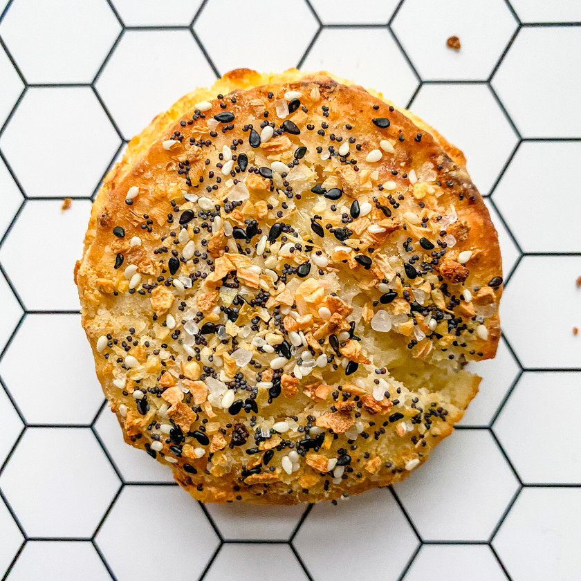 a single sourdough discard everything biscuit on a white counter