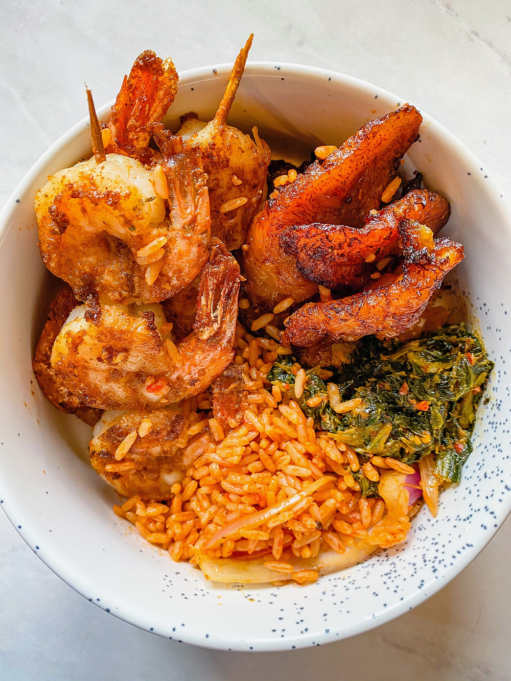 An assortment of food in a white bowl including shrimp, jollof rice, fried plantains, and sauteed greens