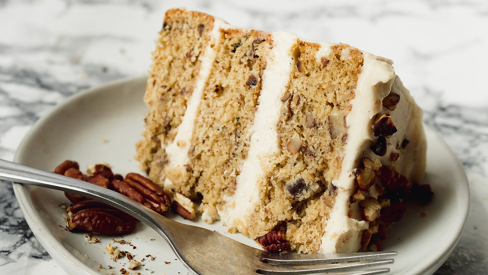 Brown butter pecan layer cake on a white plate resting on a mottled grey background with a silver fork on the plate