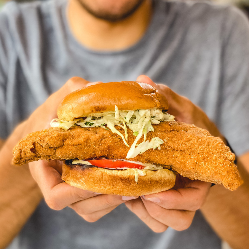 RNF Fish Sandwich: brioche bun, house made slaw and tartar sauce, and wild caught sea bass filet held up by two hands