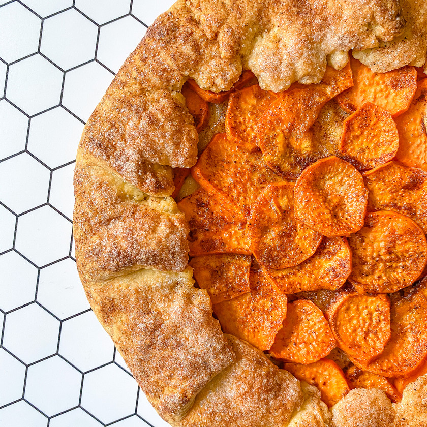 one half of a sweet potato galette up close, with a white background that has a black honeycomb design on it
