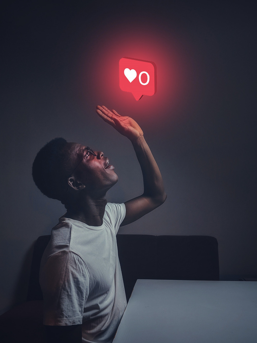 Stock photo of Black man looking upwards at a social media notification icon