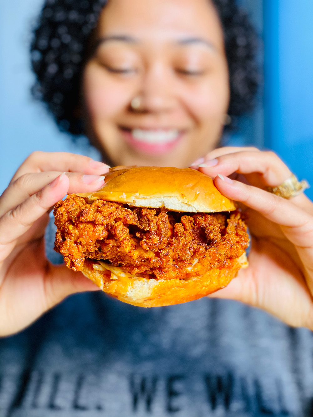 woman holding a nashville hot fried chicken sandwich and smiling