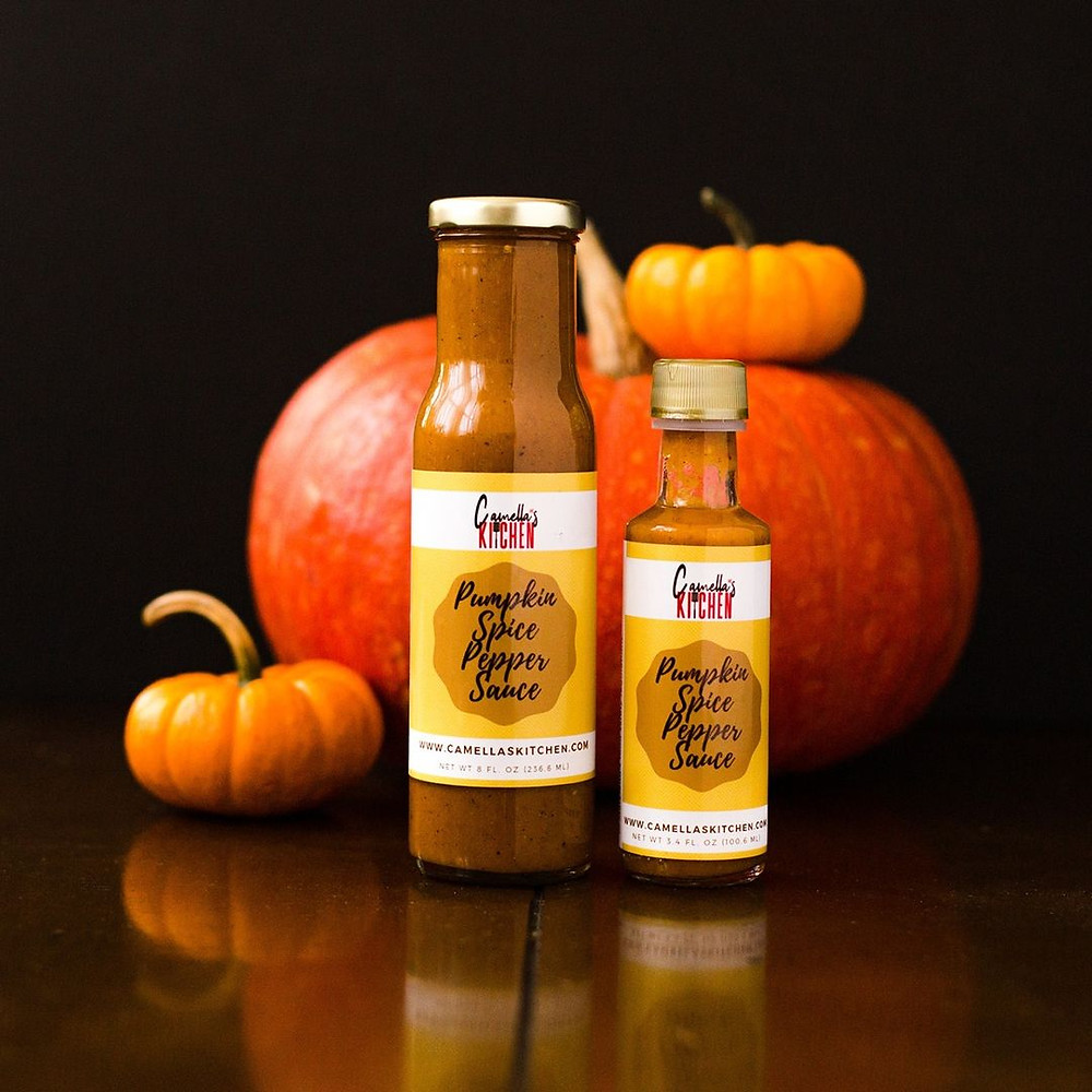Camella's Kitchen sauces in front of pumpkins and a black background
