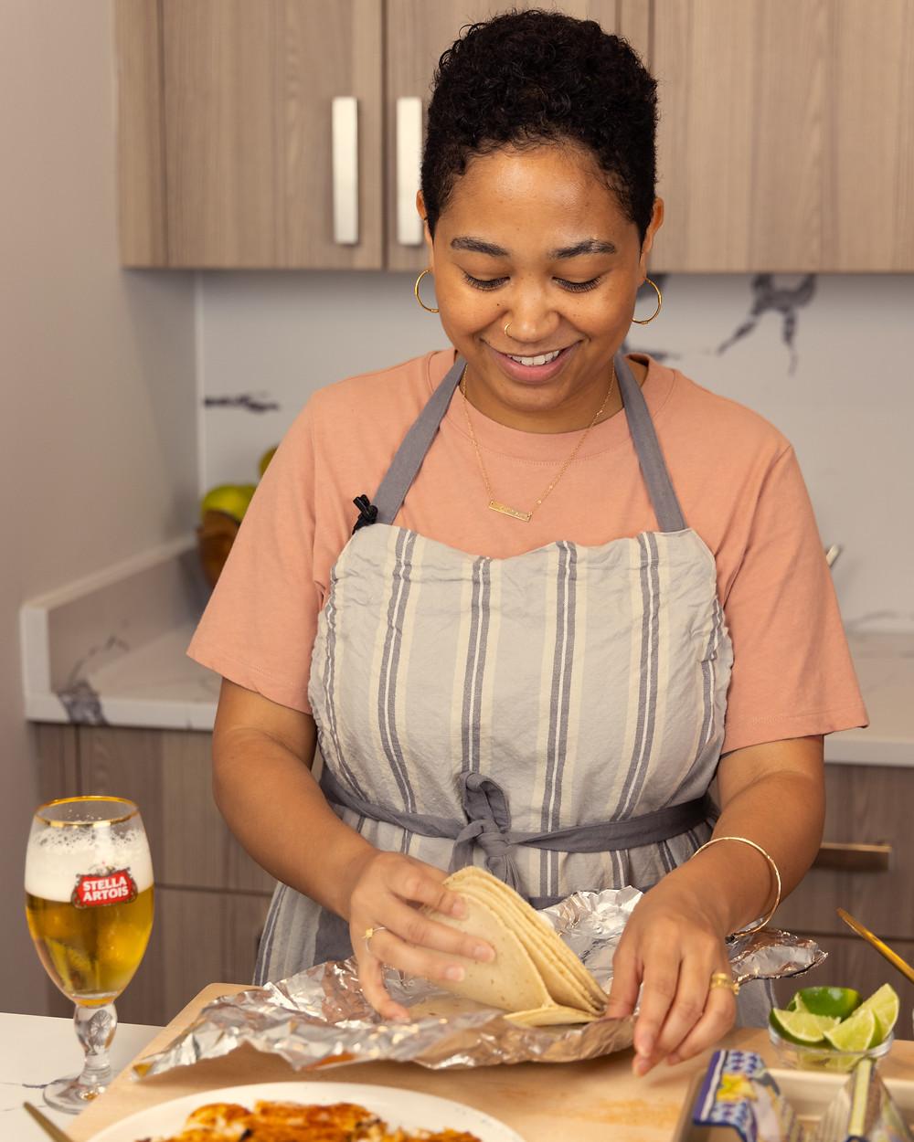 Anela prepares tortillas to go in the oven in foil