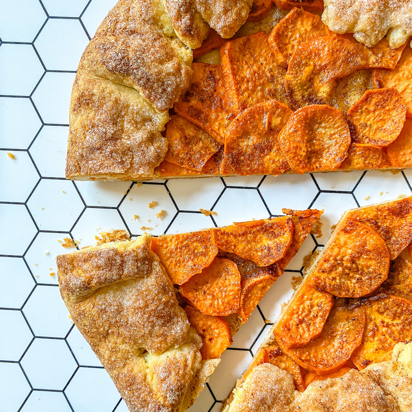 Slice of a sweet potato galette, with a white background that has a black honeycomb design on it