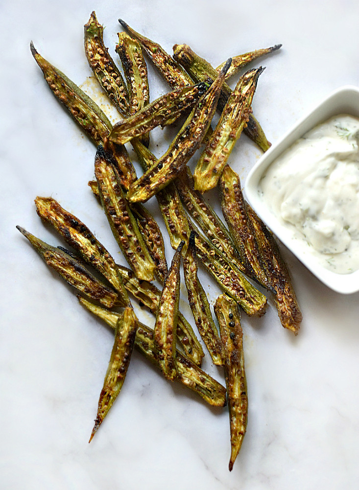 crispy okra on a white and grey mottled background with a small container of dipping aioli on the side.