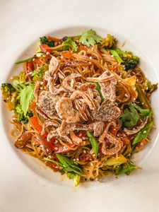 Vegetarian Fuzu: rice pasta stir fry with vegetables on a white plate