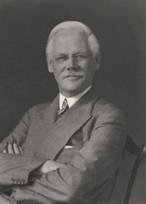 A black and white photograph of Benjamin-Seebohm Rowntree in a suit with his arms folded