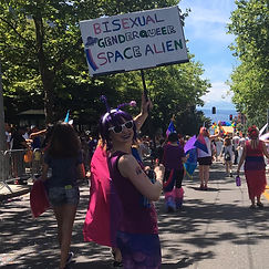 "L marching in pride, looking back and smiling, carrying a sign that reads, ""BISEXUAL GENDEQUEER SPACE ALIEN"""