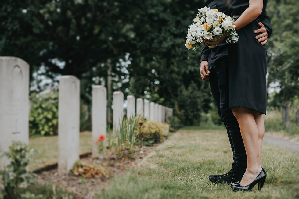 couple-standing-together-by-a-gravestone