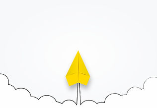Yellow Paper Airplane Soaring Through Cl
