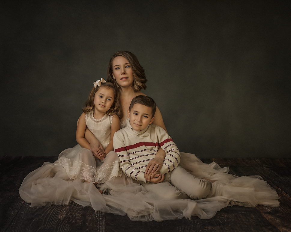 A professional photograph of a mother and her two young children, a boy and girl