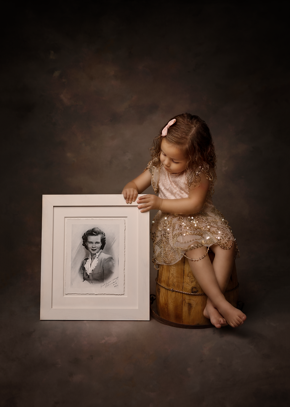 A young girl holding a photograph of her great grandmother from World War Two