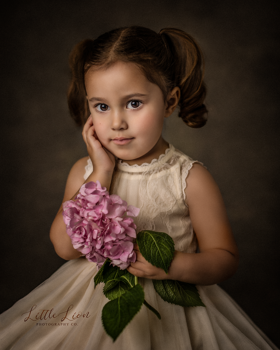 A professional photograph of a young girl holding a flower