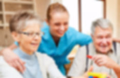 a senior center staff puts her arms around two seniors smiling