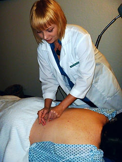 Dr. Irwin inserting acupuncture needles into a patient's back