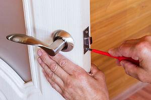carpenter-repairs-front-door-lock-fastens-handle-with-screwdriver.jpg