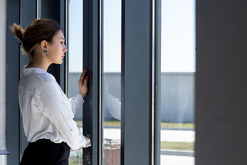 front-view-young-beautiful-lady-white-shirt-black-trousers-looking-distance-through-window