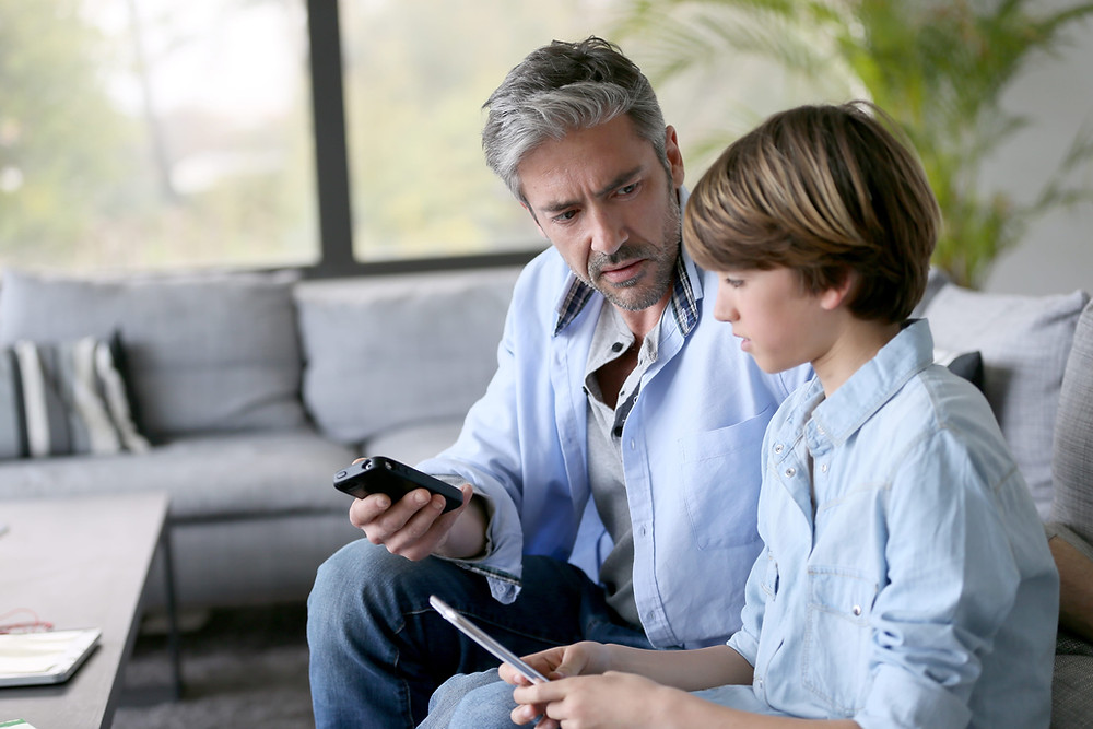 Father talking to son while holding smartphones