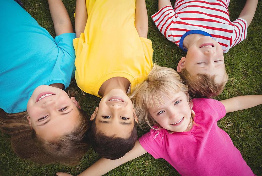 Kids laying on grass smiling