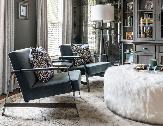 Sitting room with 2 occasional mohair blue chairs, custom drapes with a subtle pattern, concrete floor lamps against a mirrored wall, dark grey painted bookcase, and white fur ottoman