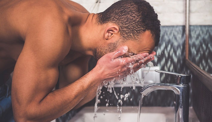 man-washing-face-at-sink-in-bathroom.jpg