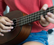 person playing ukulele during online music classes