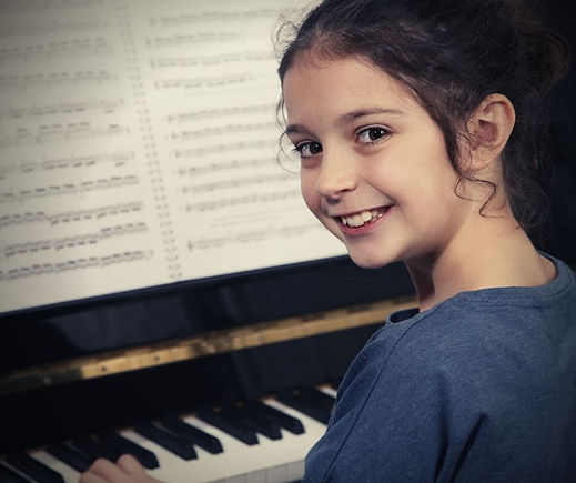 girl playing piano during online piano classes