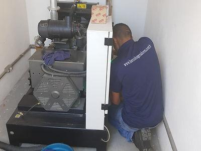 Auxiliar de manutenção da Hercules Geradores trocando peças de um gerador de energia.