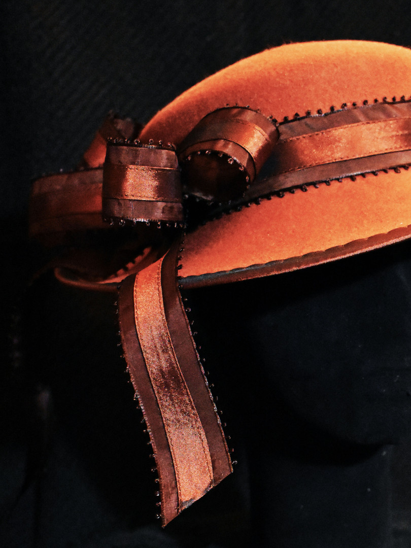 The band of this pulled felt hat is made of (made) bias ribbon topstitched to pre-made brown ribbon. The binding is prick stitched for decorative effect.