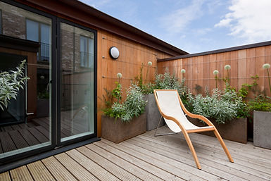 Deck with a sliding glass door & anan outdoor artifical textured wall panel
