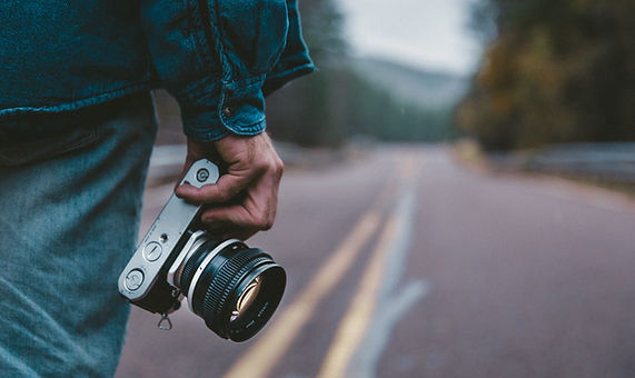 a man's hand holding a camera in th middle of th road