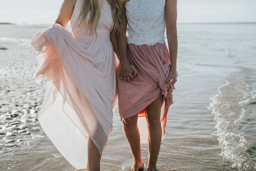 two girls wearing dresses and holding hands in the sea