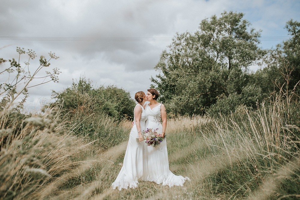 two just married brides kissing