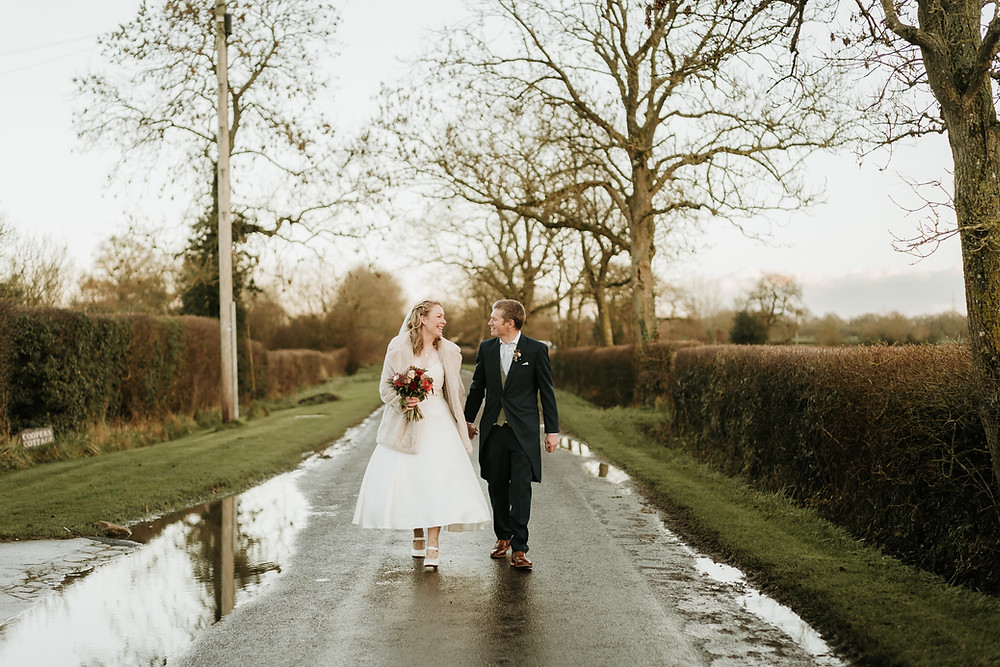 Wedding couple walking down the road in rural Wiltshire