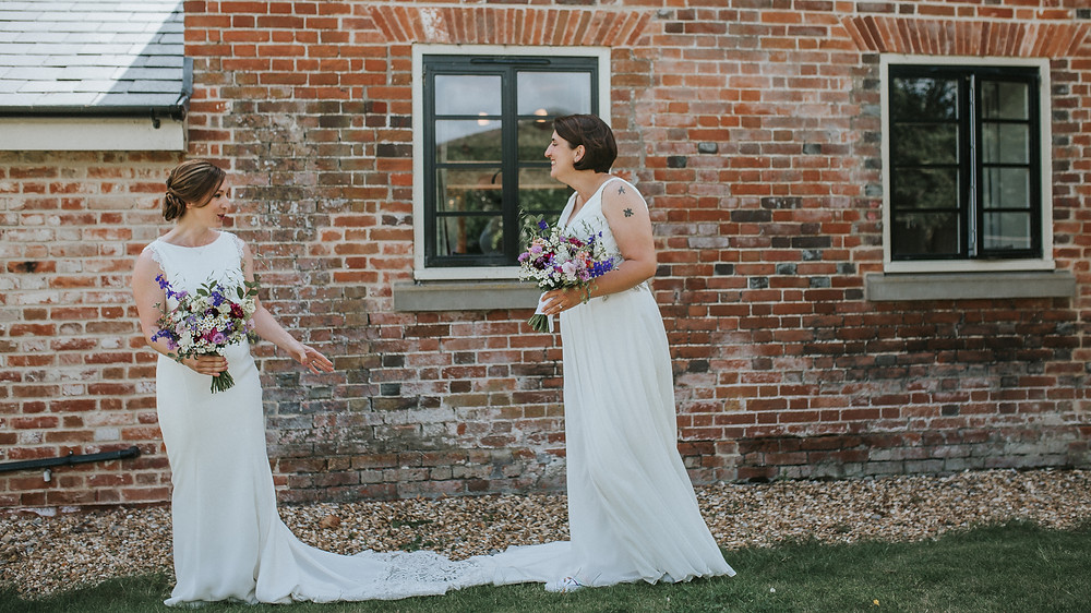 two brides seeing each other in their dresses