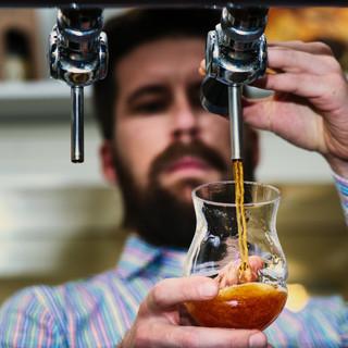 Dark draft beer poured by bartender.jpg