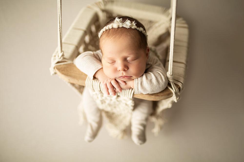 newborn baby girl in cream macrame swing at newborn photography session