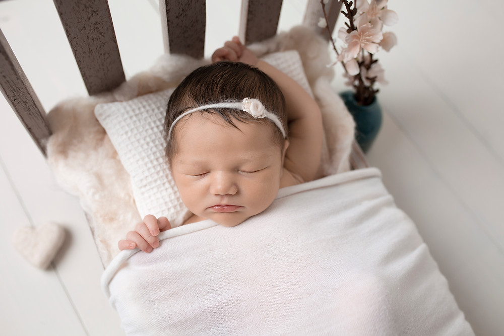 gorgeous newborn baby girl in tiny bed