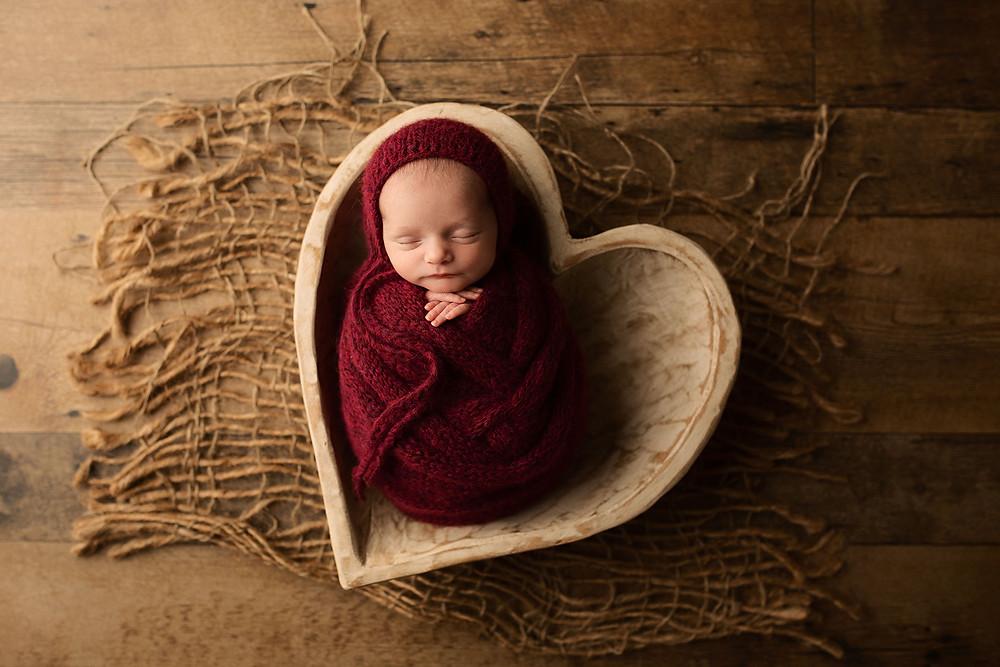 tiny 6 lb newborn baby girl in heart bowl