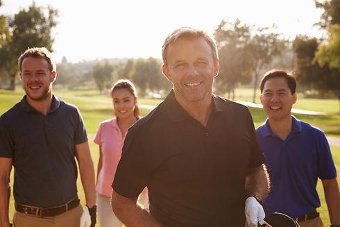 Group Of Golfers Walking Along Fairway Carrying Golf Bags.jpg
