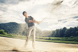 Male golf player in blue shirt and grey